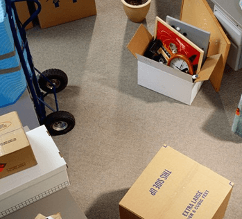 Packed moving boxes on floor with hand truck
