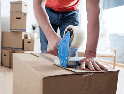 Person applying packing tape to moving box