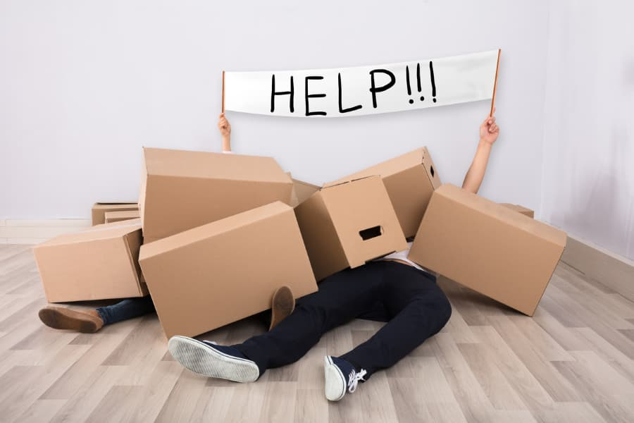 people laying under cardboard boxes in a room holding up a help sign