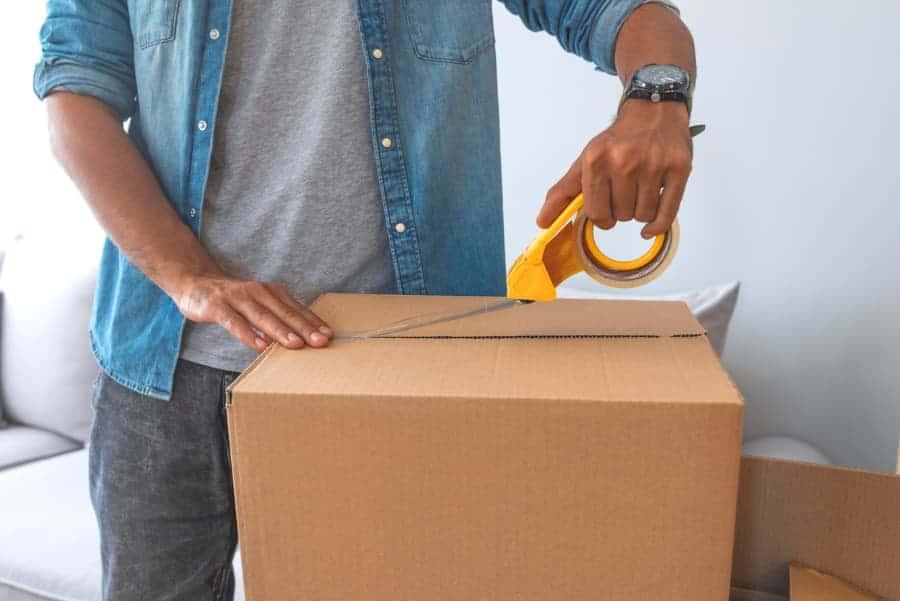 Man taping moving box shut